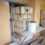 Der Grundofen wird durch die Dielen- Wohnraumwand gebaut und erwärmt so später die beiden Räume.